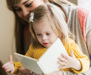 Mother (20s) reading to daughter (2 years) with down syndrome. Main focus on girl.