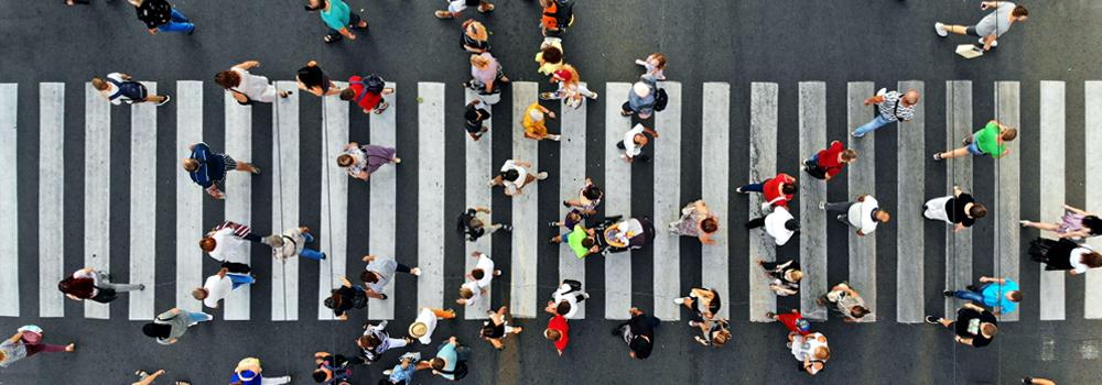 crown of people walking across a street crosswalk